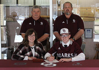 Joe Lee signing at table with mom, Roberta, and Coaches Richardson and McMillin