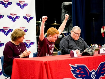 Riley Loyd with a fist pump of excitement seated at table with parents, Deana and Bob
