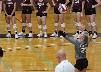 Izzy Gibbany serving the ball with the line judge in the foreground and her teammates on the sideline in the background