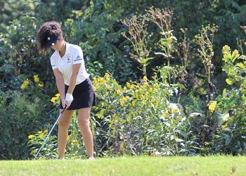 Bianca Cunningham preparing to tee off, standing on high tee box with brush and wildflowers behind her