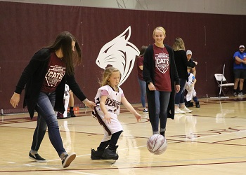 Alumni's little girl escorted by two Lady Bobcat players during a game of Dress Up Like A Bobcat