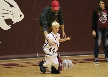 Alumni's little boy escorted by his dad during a game of Dress Up Like A Bobcat
