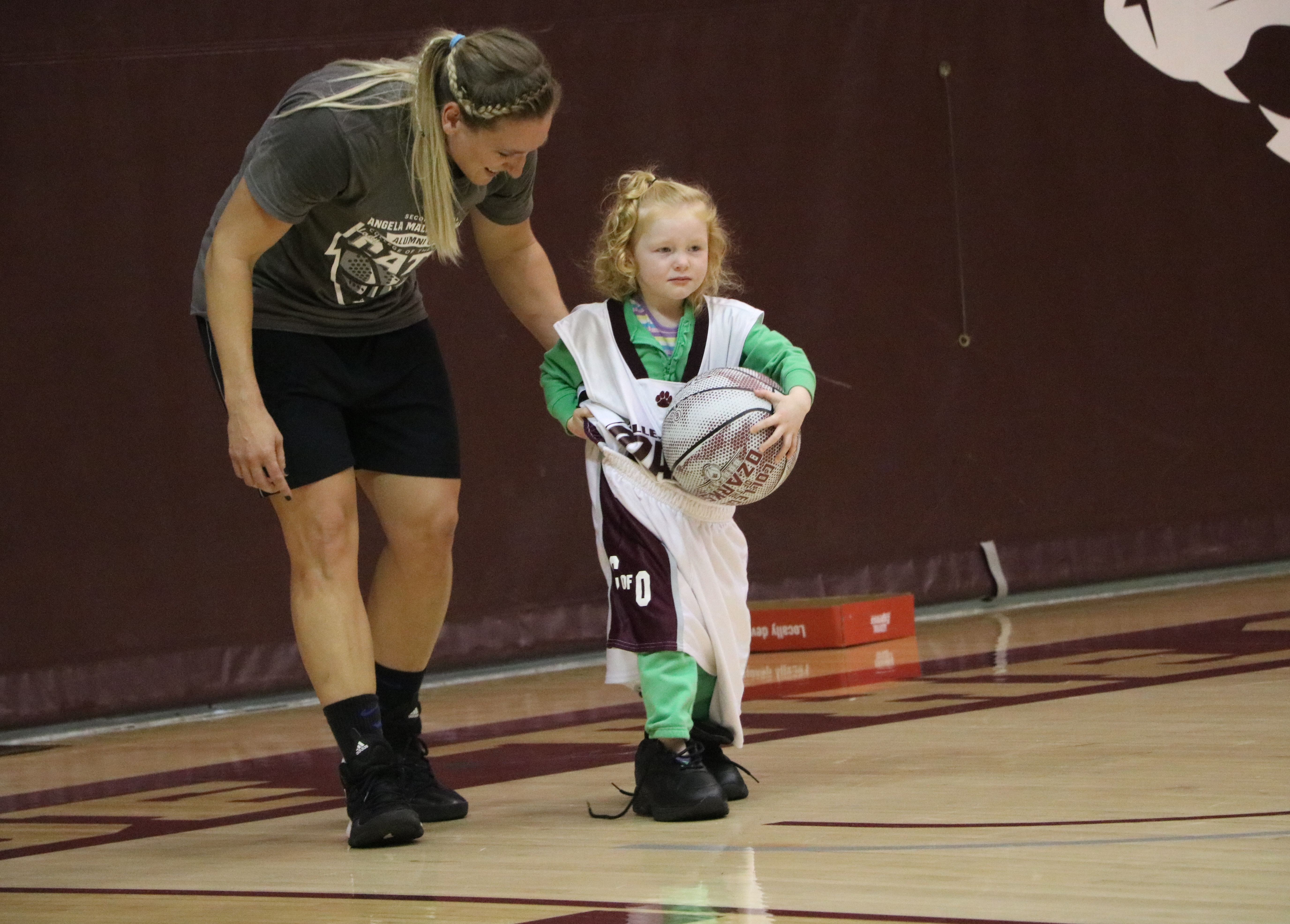 Alumni's little girl escorted bya Lady Bobcat player during a game of Dress Up Like A Bobcat