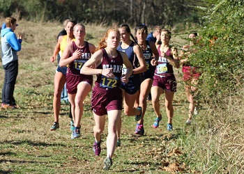 Picture of several Lady Bobcat team members and opposing runners coming around a corner of the course