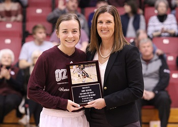 Abby Oliver and Coach  Mullis side by side holding the 1000 point commemorative plaque with fans in the stand in the background