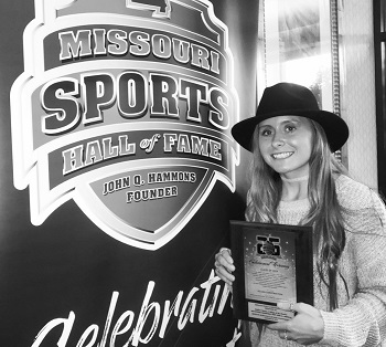 Kelsie Cleeton posing for a pic next to the MO Sports Hall of Fame sign, holding her plaque