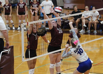 Kaylan Smith and Kaylee Larimer blocking at the net as opponent hits the ball